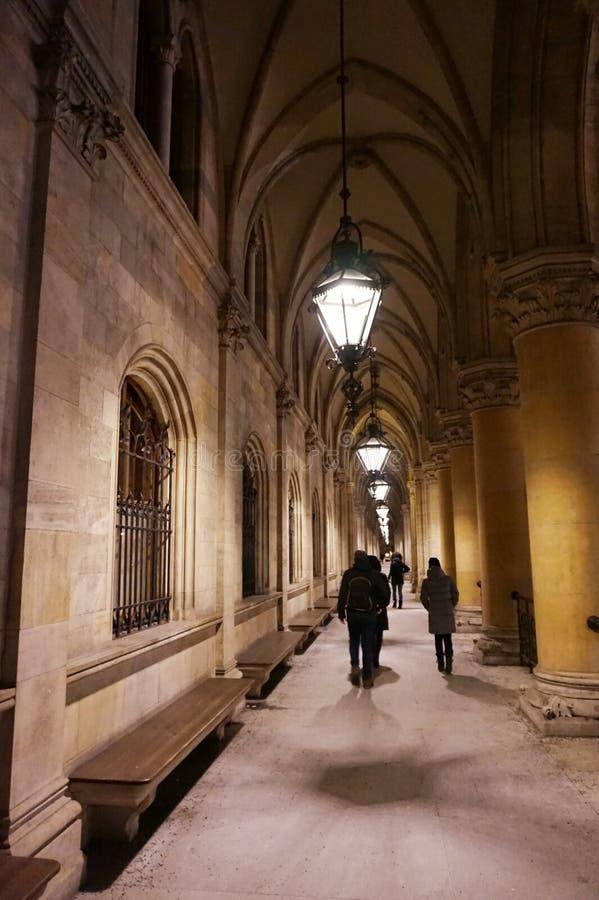 Люди идя вечером через покрытую галерею в историческом здании стоковое фото rf