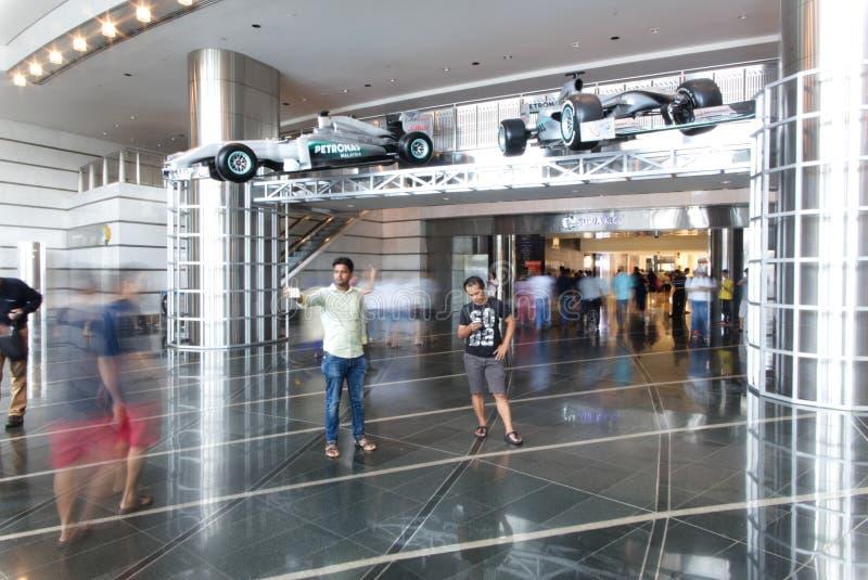 Люди идя внутрь торгового центра в башне близнецов Petronas и 2 автомобилях Формулы 1 стоковое изображение rf