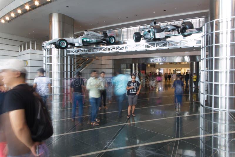 Люди идя внутрь торгового центра в башне близнецов Petronas и 2 автомобилях Формулы 1 стоковые фото