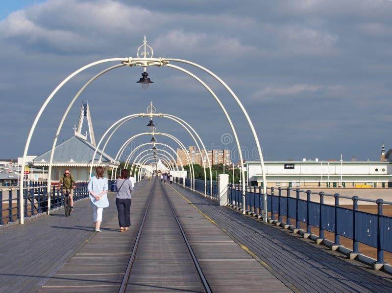 Люди идя вперед вдоль пристани в southport Мерсисайде на яркий летний день со зданиями городка против голубого облачного неба стоковое фото