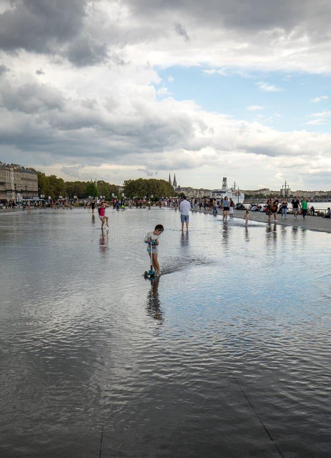 Люди идя в фонтан зеркала воды на Месте de Ла Фондовой бирже в Бордо, Аквитании, Франции стоковое изображение