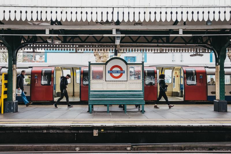 Люди идя за знаком имени станции на на открытом воздухе платформе станции метро зеленого цвета Golders, Лондона, Великобритании стоковые фото