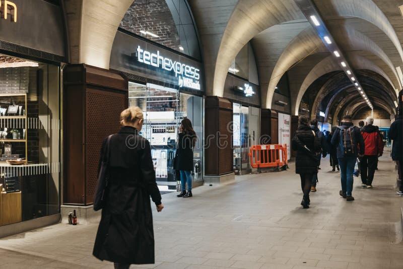 Люди идя за магазинами внутри железнодорожной станции моста Лондона, Лондона, Великобритании стоковая фотография