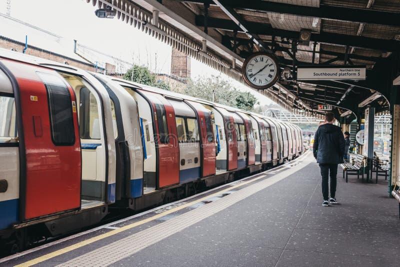 Люди идя за поездом на на открытом воздухе платформе станции метро зеленого цвета Golders, Лондона, Великобритании стоковая фотография