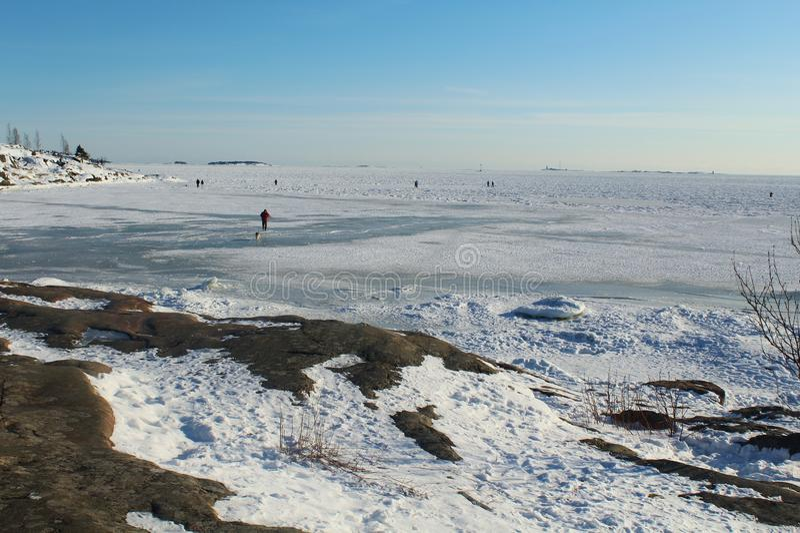 Люди идя на замороженное Балтийское море, Хельсинки, Финляндию стоковое фото rf