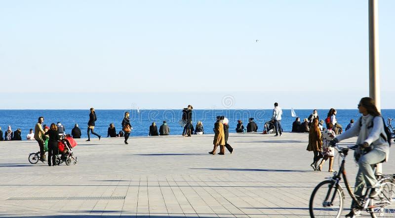 Люди идя на пляж Barceloneta стоковая фотография