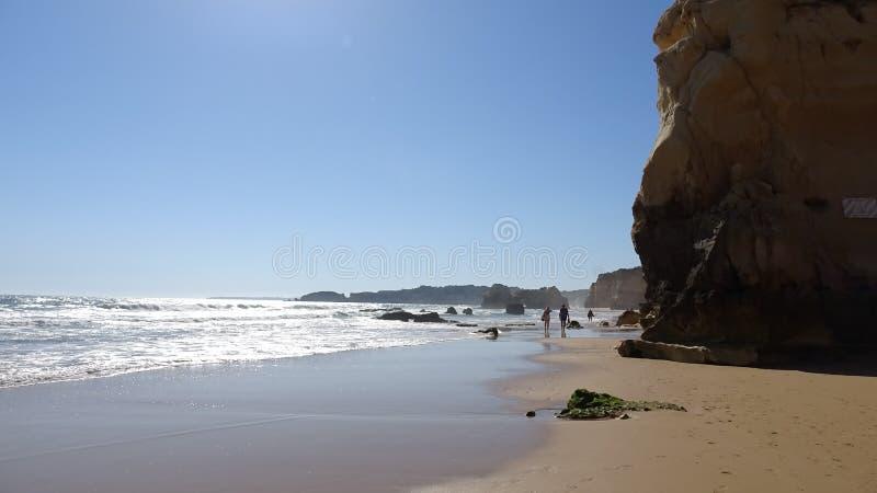 Люди идя на симпатичный пляж Алгарве в Portuga; стоковые фотографии rf