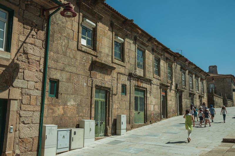 Люди идя рядом с длинным зданием сделанным камня стоковая фотография rf