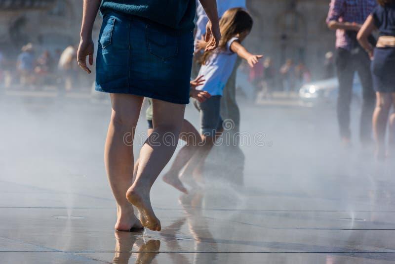 Люди имея потеху в фонтане зеркала в Бордо, Франции стоковые изображения