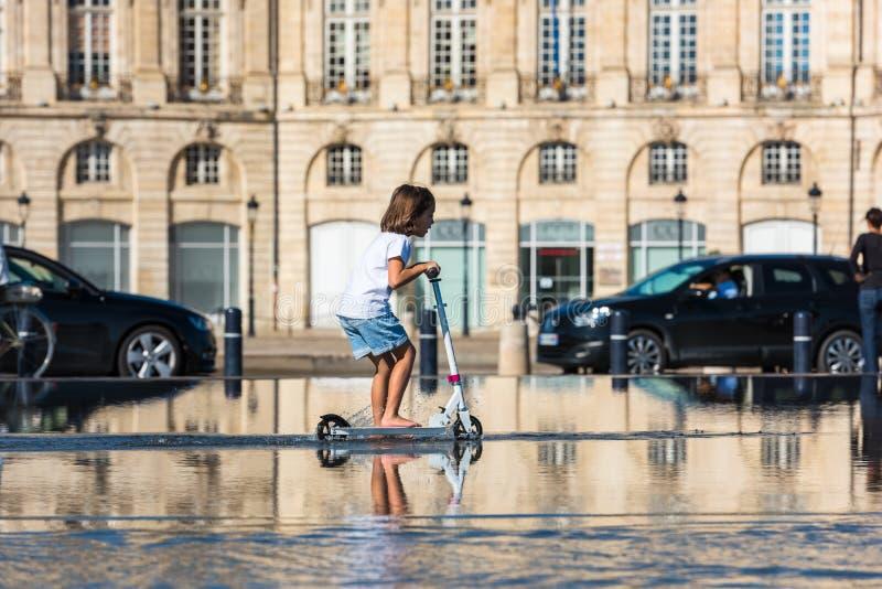 Люди имея потеху в фонтане зеркала в Бордо, Франции стоковое фото rf