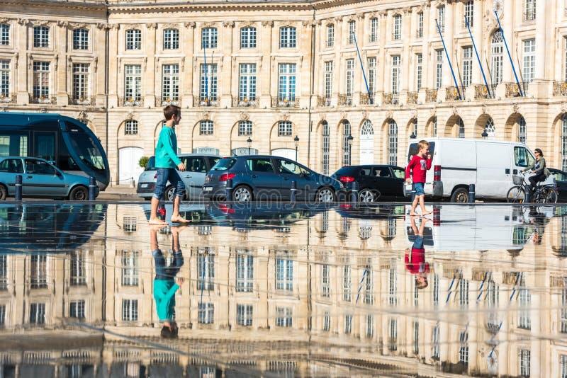 Люди имея потеху в фонтане зеркала в Бордо, Франции стоковые фото