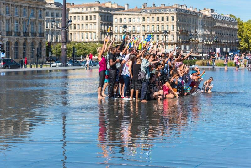 Люди имея потеху в фонтане зеркала в Бордо, Франции стоковое изображение