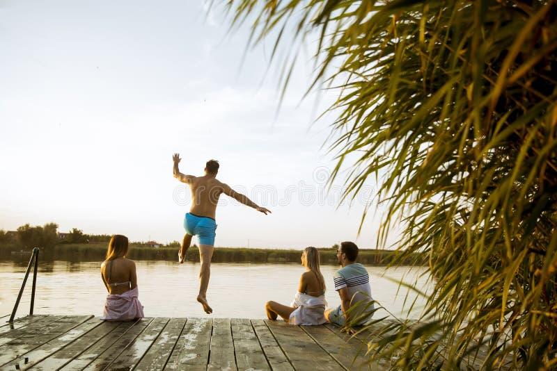 Люди имея потеху на озере на летний день стоковое фото rf