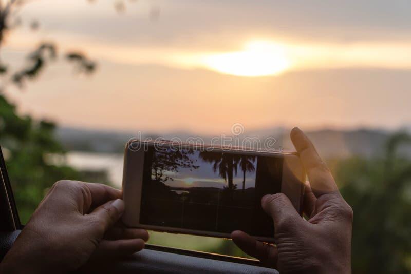 Люди используют мобильный телефон для того чтобы принять фото стоковые фотографии rf