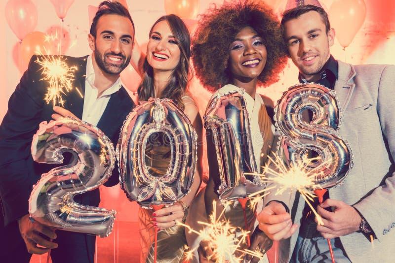 Люди и женщины празднуя Новый Год 2018 стоковое фото