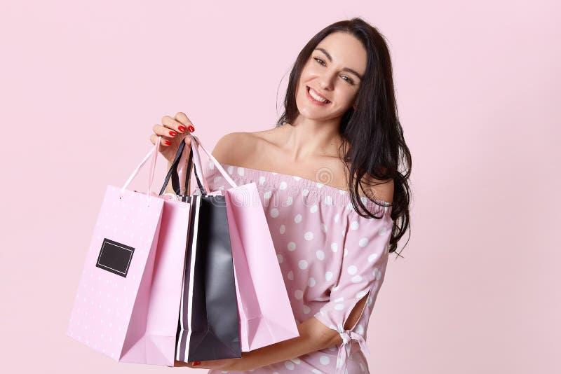 Люди и концепция покупок Счастливое темное с волосами shopaholic женщины одетое в платье точки польки, носит хозяйственные сумки, стоковое изображение rf