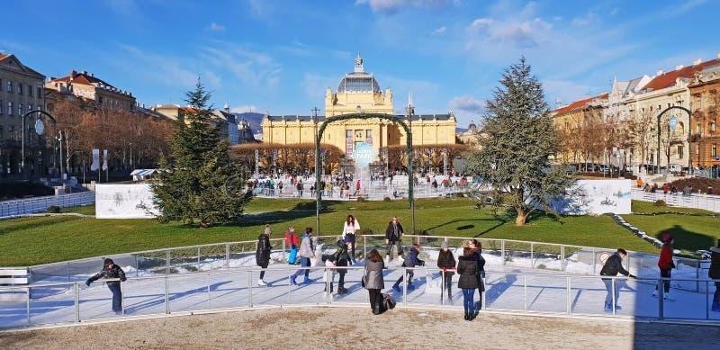 Люди катаясь на коньках на катке катания на коньках города стоковое изображение rf