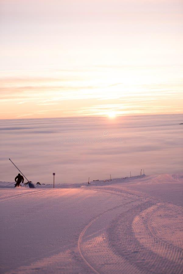 Люди катаясь на лыжах в Альпах Волшебный туман вокруг Изумительный заход солнца, идет снег совсем вокруг, красота лыжного курорта стоковое фото rf