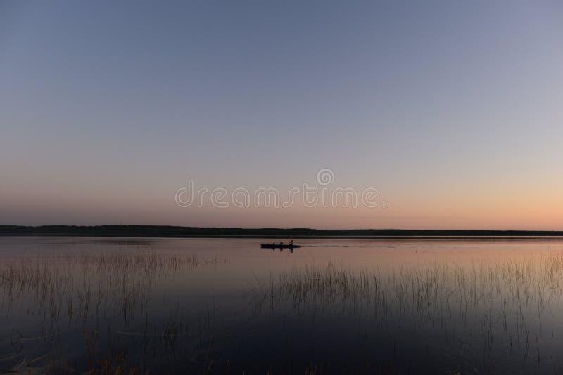 Люди Каyaking на спокойной воде озера в возвращении света захода солнца от похода стоковые изображения rf