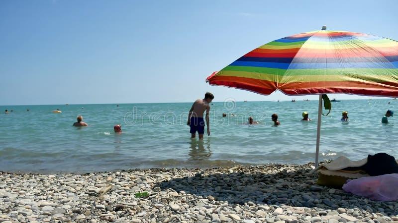 Люди купая в солнце, заплывание и играя игры на пляже E стоковое фото
