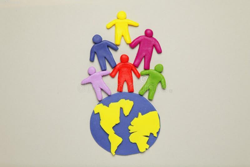 Люди мультфильма пластилина пестротканые на глобусе Польза и расход земли, перезаселенности и демографического роста планеты стоковое изображение rf