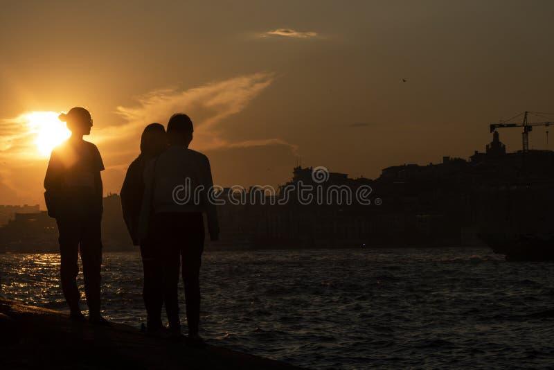 Люди наблюдая заход солнца и море стоковая фотография rf