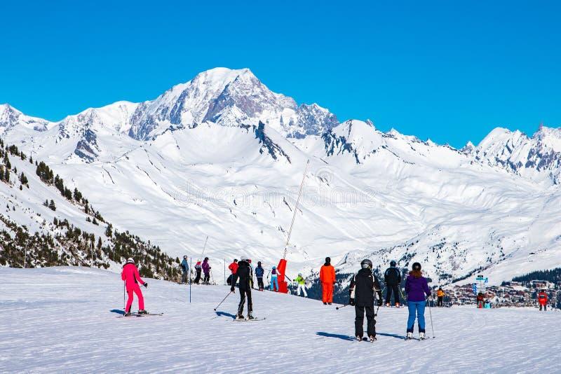 Люди наслаждаются лыжей и сноубордом на зимний отдых в зоне Альп с Монбланом как предпосылка, дуги 2000 Les, Савойя, Франция, стоковое фото