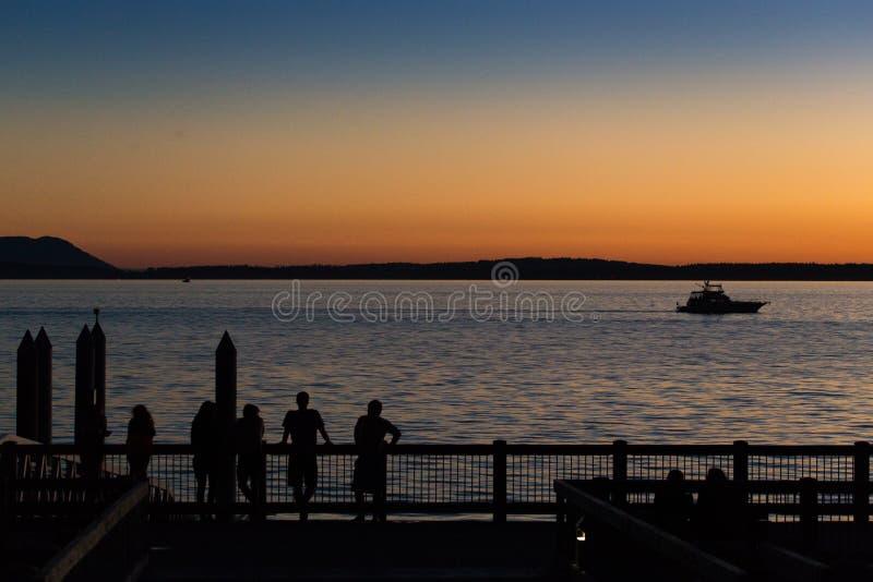 Люди наслаждаясь заходом солнца на пристани моря стоковая фотография rf