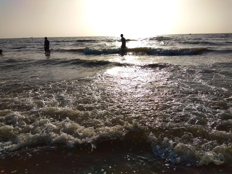 Люди наслаждаясь набором Солнца с морской водой стоковые фотографии rf