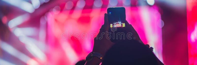 Люди наслаждаясь рок-концертом и принимая фото с сотовым телефоном на ЗНАМЯ музыкального фестиваля, длинным форматом стоковое фото rf