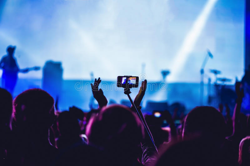 Люди наслаждаясь рок-концертом и принимая фото с сотовым телефоном a стоковые изображения rf