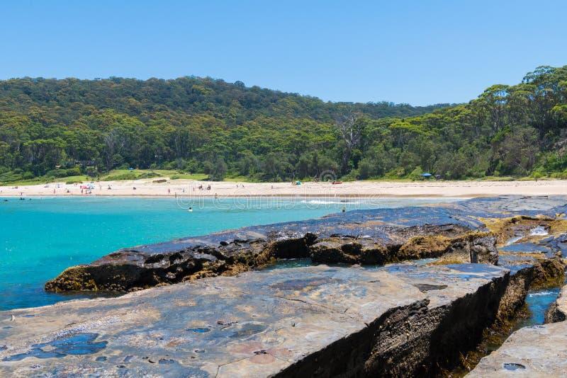 Люди наслаждаясь солнечной погодой на Pebbly пляже, популярной располагаясь лагерем зоной с большим занимаясь серфингом пляжем и  стоковое фото rf