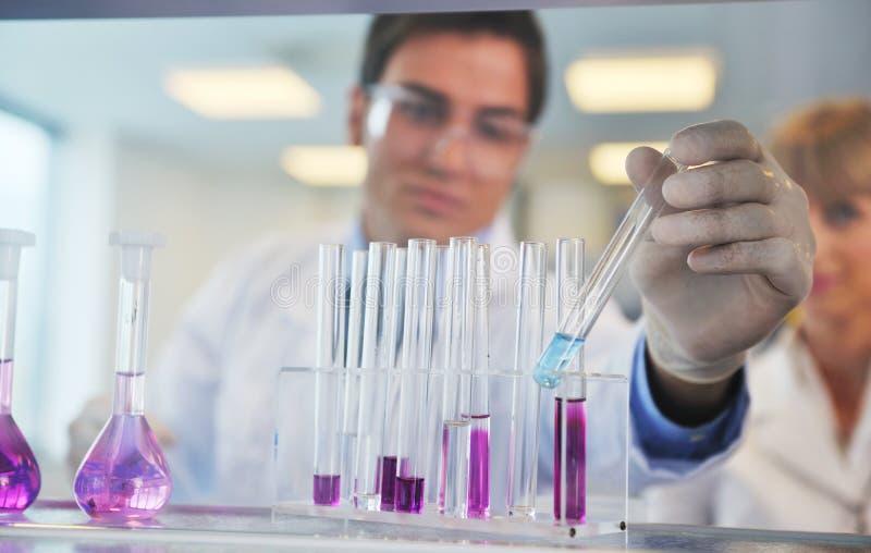 Люди науки в яркой лаборатории стоковое фото