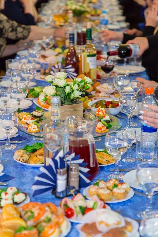 Люди на банкете Торжественное событие в предприятии Годовщина или свадьба Закуски и спирт на таблицах стоковое фото rf