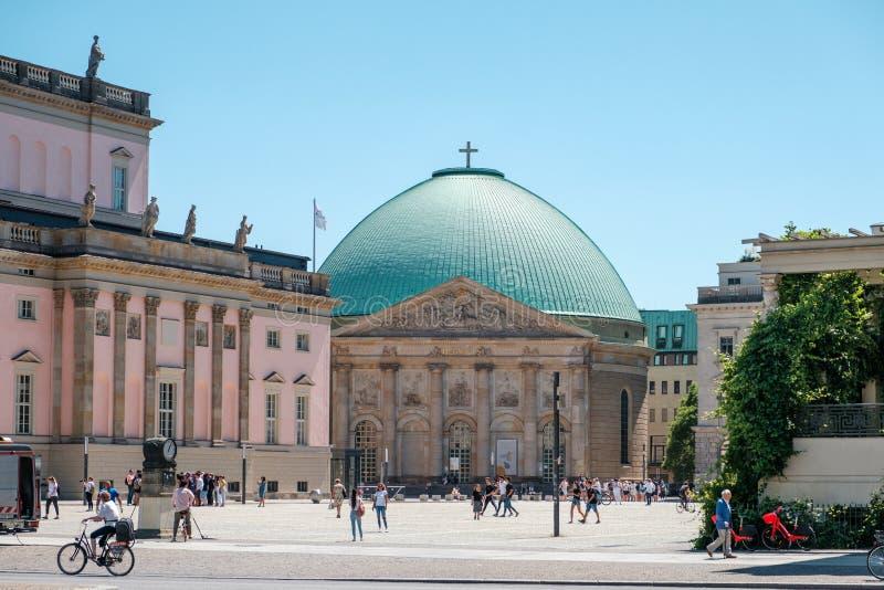 Люди на историческом районе Bebelplatz Берлина в шрифте здания государственной оперы и собора St hedwig стоковые изображения rf
