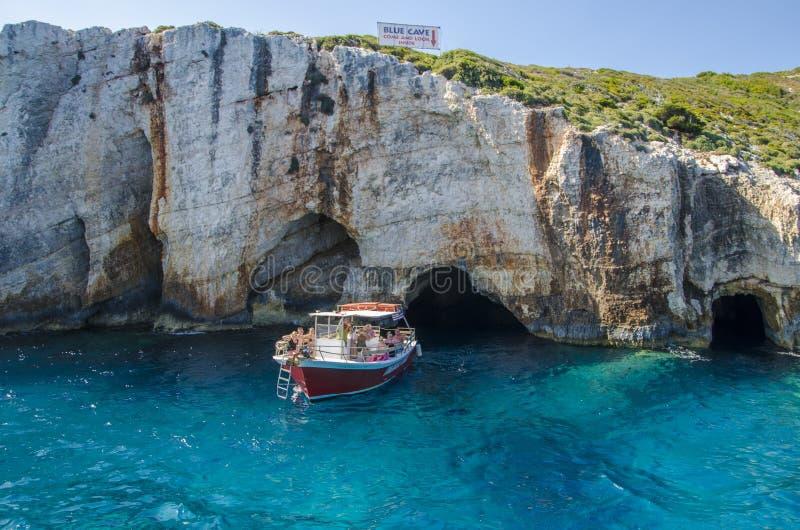 Люди на моторной лодке наслаждаясь прогулкой на яхте к известным естественным голубым пещерам стоковые фотографии rf
