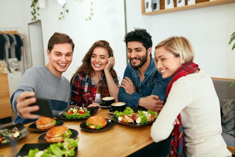 Люди на обедающем принимая фото на телефоне Видео друзей вызывать стоковое изображение