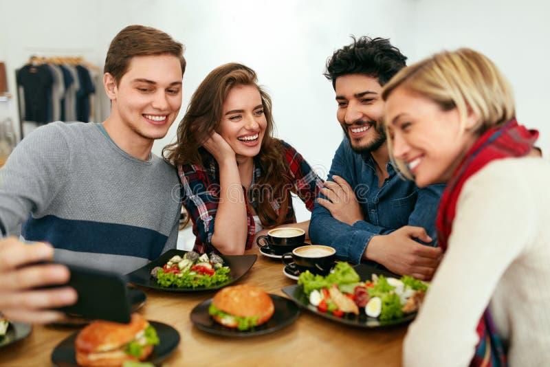 Люди на обедающем принимая фото на телефоне Видео друзей вызывать стоковые фото