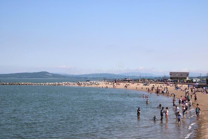 Люди на пляже, солнечном дне, Morecambe, Lancashire стоковые фотографии rf