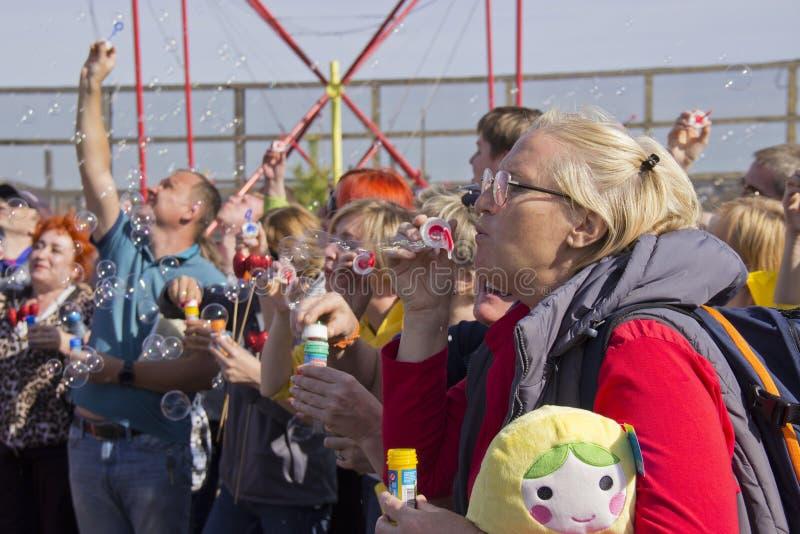 Люди на пузырях дуновения праздника стоковое фото rf