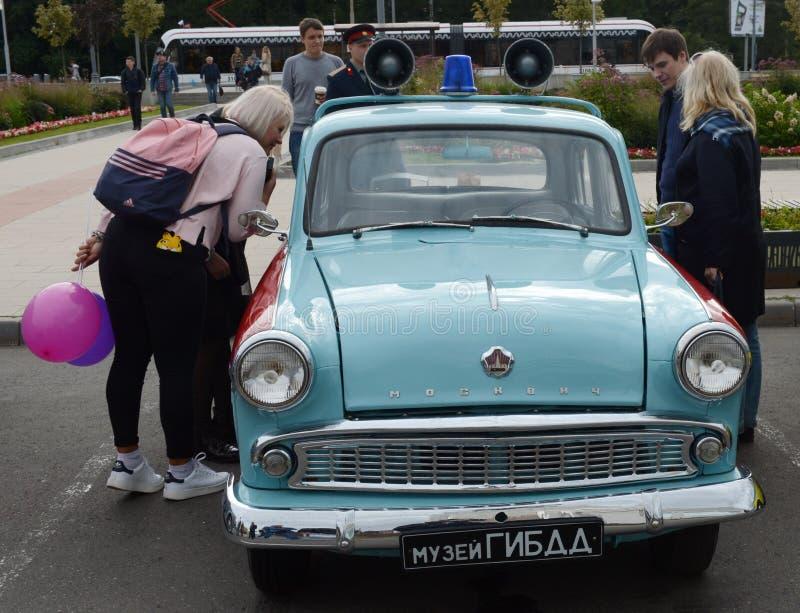 Люди на старом советском ` Moskvich -403 ` полицейской машины на выставке старых автомобилей стоковая фотография