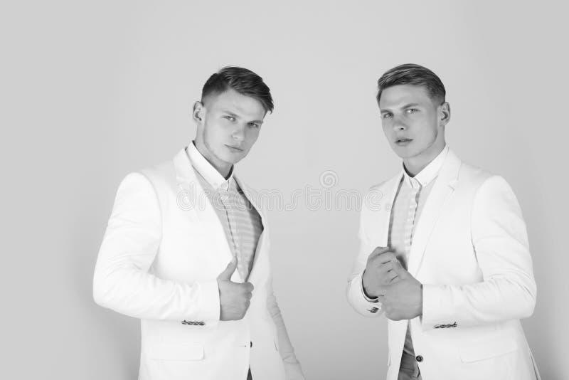 Люди нося белые куртки на серой предпосылке стоковая фотография