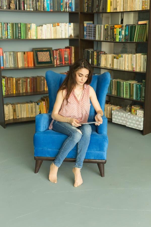 Люди, образование и концепция технологии - милая молодая студентка используя планшет в библиотеке стоковое фото