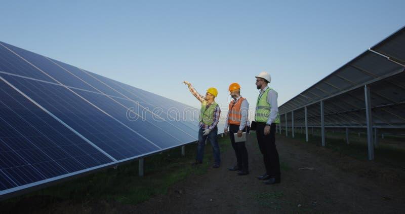 Люди обсуждая панели солнечных батарей на поле плантации стоковое изображение