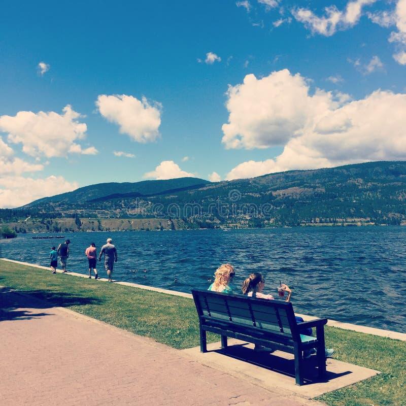 Люди ослабляя на береге озера стоковая фотография