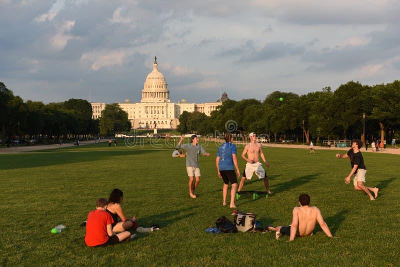 Люди отдыхают и играют шарик на национальном моле с капитолием Соединенных Штатов на предпосылке стоковые изображения