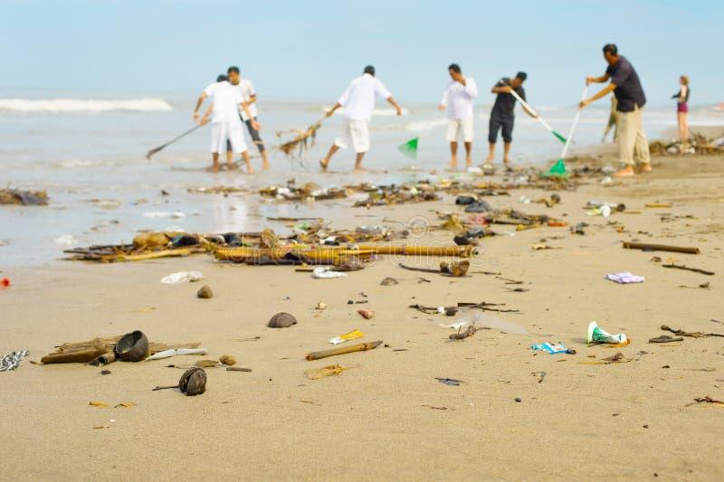 Люди очищая загрязнянный пляж тюкованный стоковые изображения