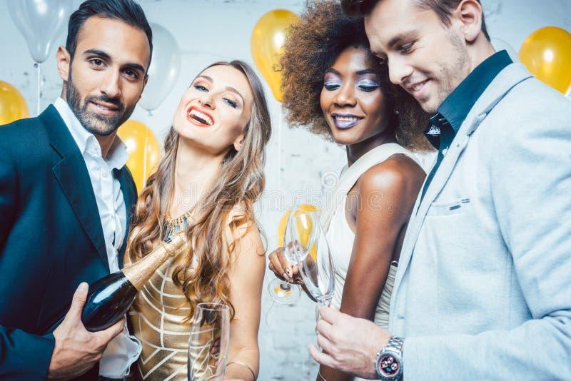 Люди партии в шампанском клуба празднуя и лить стоковое фото rf