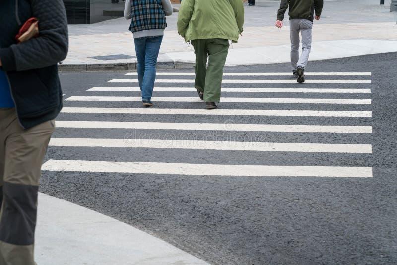 Люди пересекают дорогу на пешеходном переходе стоковое изображение