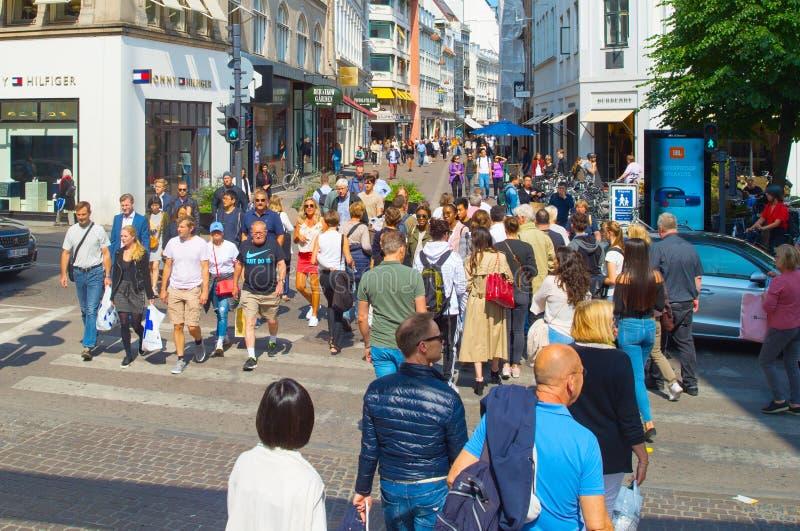 Люди пересекая торговую улицу Копенгагена стоковое изображение